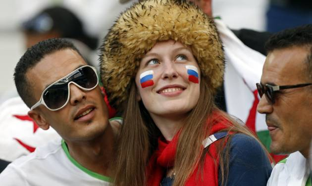 Russian, center,  and Algerian fans have their picture taken before the group H World Cup soccer match between Algeria and Russia at the Arena da Baixada in Curitiba, Brazil, Thursday, June 26, 2014. (AP Photo/Jon Super)