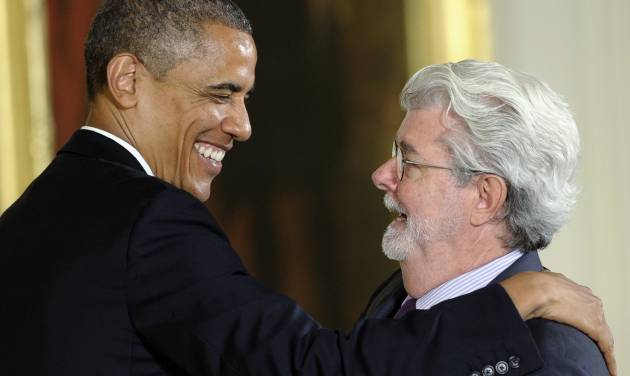 President Barack Obama hugs director George Lucas before presenting him with the 2012 National Medal of Arts, Wednesday, July 10, 2013, during a ceremony in the East Room of White House in Washington,. (AP Photo/Susan Walsh)