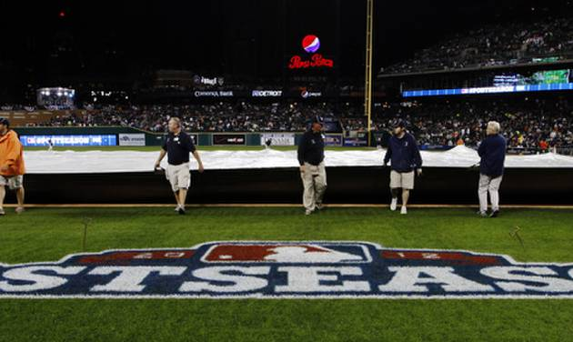 Grounds crew members cover the field during a rain delay at Game 4 of the American League championship series between the Detroit Tigers and New York Yankees Wednesday, Oct. 17, 2012, in Detroit. (AP Photo/Paul Sancya )