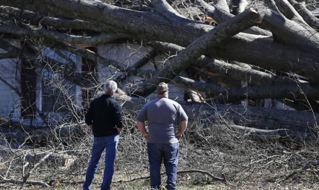 Two men stand next to a tree that covered damaged house , Wednesday, March 2, 2016, after a storm ripped through Bessemer, Ala., on Tuesday evening. Forecasters say a tornado that severely damaged homes and trees in the Birmingham suburb has been determined as an EF2, with winds of between 120 and 125 mph.  (AP Photo/Brynn Anderson)