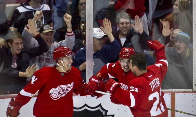 Detroit Red Wings forward Luke Glendening, left, and forward Tomas Tatar (21), of Slovakia, celebrate with forward Tomas Jurco (26), also of Slovakia, after Jurco's goal in the third period of an NHL hockey game against the Boston Bruins in Detroit, Mich., Wednesday, April 2, 2014. The Red Wings won 3-2. (AP Photo/Tony Ding)