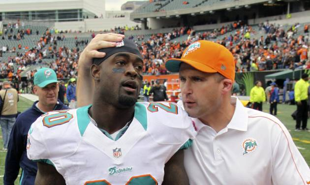 Miami Dolphins free safety Reshad Jones (20) walks off the field with special teams coach Darren Rizzi after the Dolphins defeated the Cincinnati Bengals in an NFL football game on Sunday, Oct. 7, 2012, in Cincinnati. Jones made an interception in the closing minute of the game to seal the win. (AP Photo/Tom Uhlman)