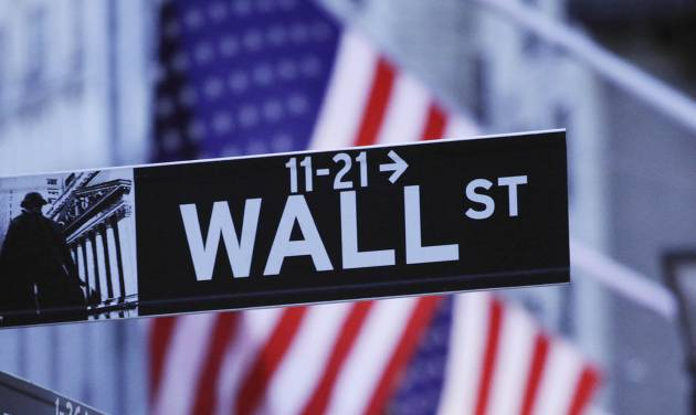 FILE - In this Aug. 9, 2011 file photo, American flags hang behind a Wall Street sign outside the New York Stock Exchange, in New York. World stock markets were mostly weaker Friday, May 30, 2014, after a government report showed the U.S. economy shrank in the first quarter and the U.S. dollar lost value against major Asian currencies. (AP Photo/Mark Lennihan, File)
