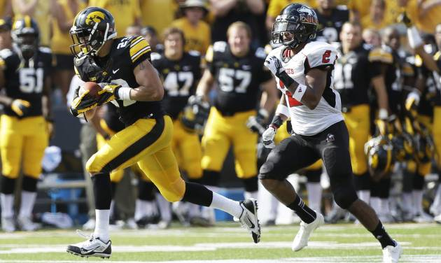 Iowa wide receiver Jordan Cotton, left, runs from Northern Illinois cornerback Sean Evans after catching a 53-yard pass during the first half of an NCAA college football game, Saturday, Aug. 31, 2013, in Iowa City, Iowa. (AP Photo/Charlie Neibergall)