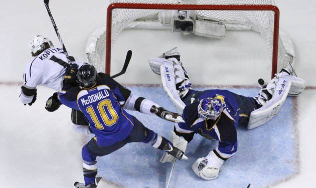 Los Angeles Kings' Anze Kopitar, left, of Slovenia, scores past St. Louis Blues goalie Brian Elliott, right, and Blues' Andy McDonald (10) during the first period in Game 2 of an NHL second-round playoff series hockey game on Monday, April 30, 2012, in St. Louis. (AP Photo/Jeff Roberson)