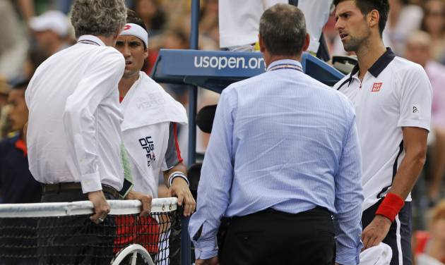 Spain's David Ferrer, second from left, and Serbia's Novak Djokovic, far right, talk with officials during a semifinal match at the 2012 US Open tennis tournament, Saturday, Sept. 8, 2012, in New York. The match was suspended in the first set because of approaching inclement weather. (AP Photo/Mike Groll)