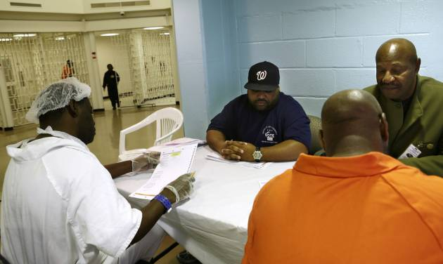 In this photo taken Oct. 24, 2012, Arlin Budoo, center, and Tyrone Parker, right, help prisoners to vote at the D.C. Jail in Washington. The voters at this southeast Washington polling place were all dressed alike: orange jumpsuit, white shoes. And when they finished voting they went back to their cell block, not back to work. Still, voting inside the D.C. Jail looked a lot like voting at precincts around the country.(AP Photo/Jacquelyn Martin)