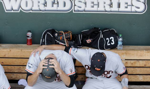 Oregon State's Matt Boyd, left, and Nate Esposito sit in the dugout after losing 4-1 to Mississippi State in an NCAA College World Series baseball game in Omaha, Neb., Friday, June 21, 2013. Mississippi State advances to the championship series and Oregon State is eliminated. (AP Photo/Francis Gardler)