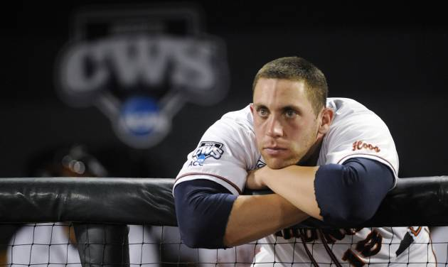 Virginia catcher Nate Irving watches as Vanderbilt players celebrate after Vanderbilt defeated Virginia 3-2 in the deciding game of the best-of-three NCAA baseball College World Series finals in Omaha, Neb., Wednesday, June 25, 2014. (AP Photo/Eric Francis)
