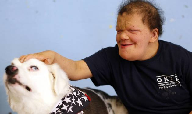 Amanda Holland pets Whiskey as the therapy dog visits the Oklahoma Foundation for the Disabled in Oklahoma City. Photo by Sarah Phipps, The Oklahoman   SARAH PHIPPS -