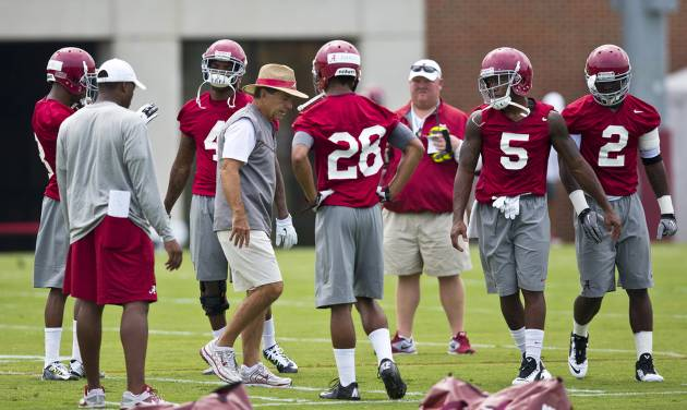 Alabama head coach Nick Saban, center, stands with the team during an NCAA college football practice, at the Thomas-Drew practice fields on Friday, Aug. 1, 2014, in Tuscaloosa, Ala. (AP Photo/Brynn Anderson)