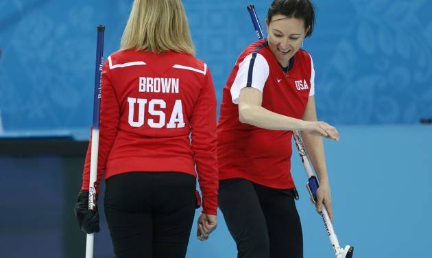 Team USA's Ann Swisshelm, right, pats skip Erika Brown on the behind after a good throw during a women's curling training session the 2014 Winter Olympics, Sunday, Feb. 9, 2014, in Sochi, Russia. (AP Photo/Robert F. Bukaty)