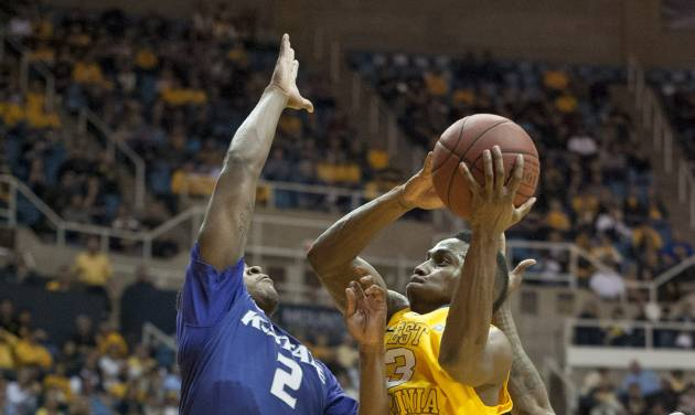 West Virginia's Juwan Staten, right, drives to the basket as Kansas State's Marcus Foster defends during the second half of an NCAA college basketball game Saturday, Feb. 1, 2014, in Morgantown, W.Va. West Virginia won 81-71. (AP Photo/Andrew Ferguson)