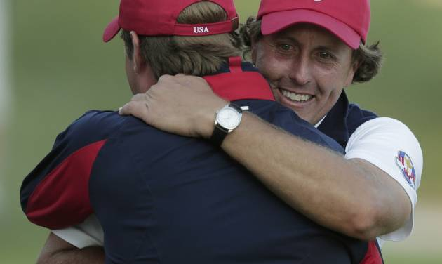 USA's captain Davis Love III hugs Phil Mickelson on the 17th hole after winning a four-ball match at the Ryder Cup PGA golf tournament Friday, Sept. 28, 2012, at the Medinah Country Club in Medinah, Ill. (AP Photo/Charlie Riedel)