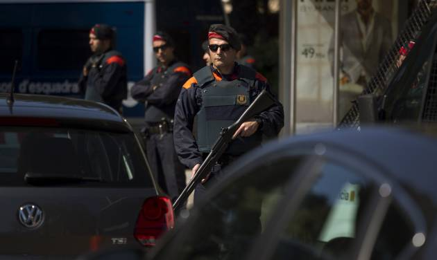 A police officer hold a weapon in a checkpoint near the hotel where the meeting of the European Central Bank is taking place in Barcelona, Spain, Thursday, May 3, 2012. European stocks pushed ahead Thursday after cash-strapped Spain got through another set of bond auctions unscathed and ahead of the latest policy statement from the European Central Bank's president Mario Draghi. (AP Photo/Emilio Morenatti)