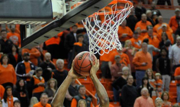 Oklahoma State guard Marcus Smart scores against West Virginia during an NCAA college basketball game in Stillwater, Okla., Saturday, Jan. 26, 2013. (AP Photo/Tulsa World, KT King)  ONLINE OUT; TV OUT; TULSA OUT