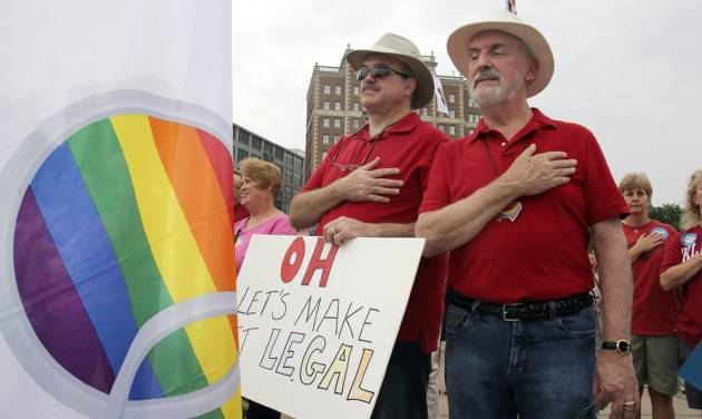 Gay marriage supporters Duane Lewis and Rex Van Alstine, right, hold their hands to their chest as the national anthem plays during a rally in support of gay marriage in downtown Cincinnati, Tuesday, Aug. 5, 2014. The Cincinnati-based 6th U.S. Circuit Court of Appeals will hear arguments in six gay marriage fights from Ohio, Michigan, Kentucky and Tennessee on Wednesday, setting the stage for one ruling. (AP Photo/Tom Uhlman)