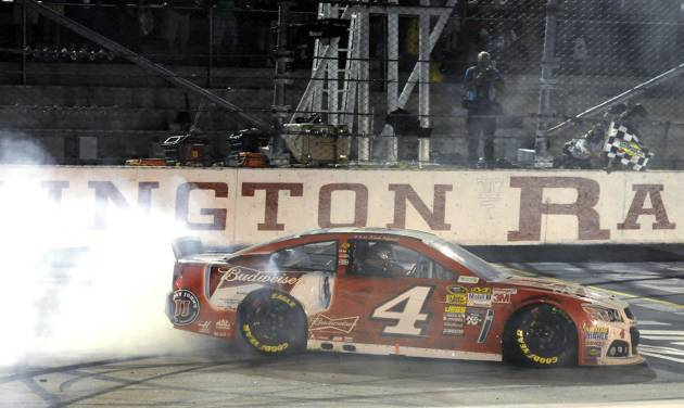 Kevin Harvick does a burnout after winning the NASCAR Sprint Cup auto race at Darlington Raceway in Darlington, S.C., Saturday, April 12, 2014. (AP Photo/Mike McCarn)