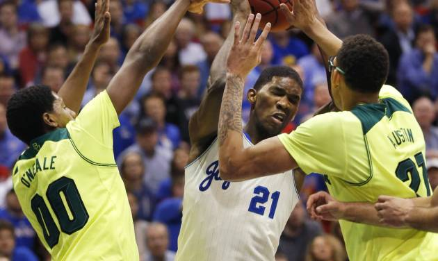 Kansas center Joel Embiid (21) looks for a shot while covered by Baylor forward Royce O'Neale (00) and center Isaiah Austin (21) during the first half of an NCAA college basketball game in Lawrence, Kan., Monday, Jan. 20, 2014. (AP Photo/Orlin Wagner)