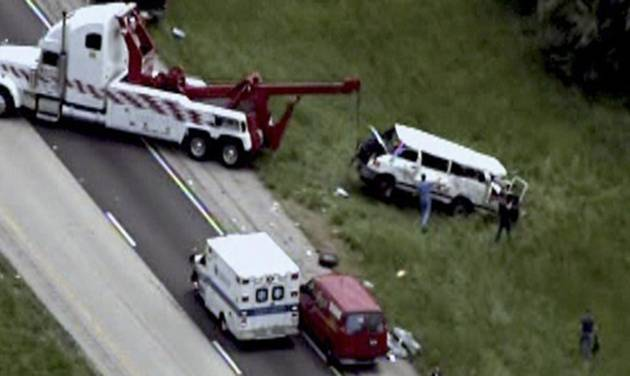 This photo from video provided by KMOV-TV in St. Louis shows emergency personnel at the scene near Vandalia, Ill., Monday, May 20, 2013, where a van veered off a southern Illinois highway and overturned several times, killing five people and sending six others to hospitals, authorities said. Details about what caused the crash or who owned the white 2002 Dodge van, which had no decals or displayed markings, were not immediately available. (AP Photo/Courtesy KMOV-TV in St. Louis)  ST LOUIS POST DISPATCH OUT. TV OUT