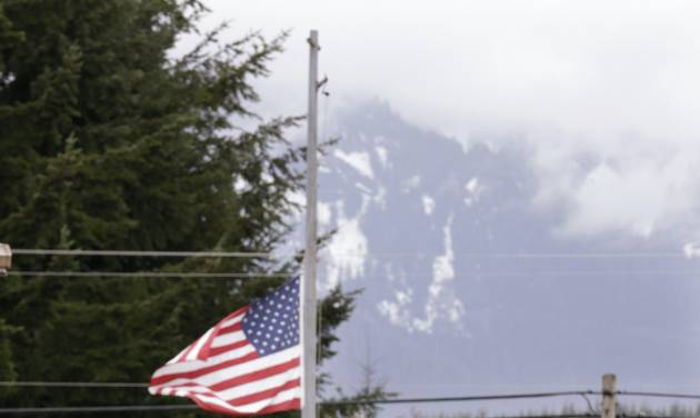 A road sign advising the closure of Highway 530 stands in view of a flag still at half-staff Tuesday, April 15, 2014, in Darrington, Wash. One more victim has been recovered from the mudslide that hit the nearby town of Oso, Wash., March 22, raising the death toll to 37, the Snohomish County medical examiner's office said Tuesday. Seven people remain on the missing list, the sheriff's office said. (AP Photo/Elaine Thompson)