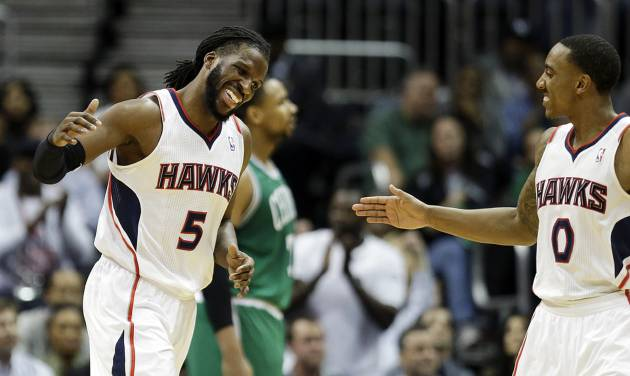 Atlanta Hawks' DeMarre Carroll, left, high-fives teammate Jeff Teague after scoring a basket in the fourth quarter of an NBA basketball game against the Boston Celtics, Wednesday, April 9, 2014, in Atlanta. Atlanta won 105-97. (AP Photo/David Goldman)