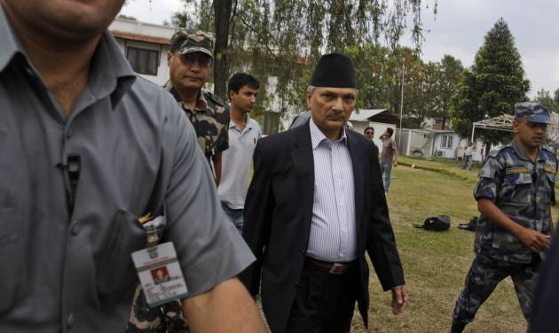 Nepal's Prime Minister Baburam Bhattarai, second right, walks escorted by security officers after meeting with leaders of major political parties in Katmandu, Nepal, Thursday, May, 3, 2012. In a last-ditch effort to finish years of work on Nepal's new constitution, Prime Minister Bhattarai will dissolve his Cabinet and form a new coalition government that includes members of the main opposition parties, an aide said Thursday. (AP Photo/Binod Joshi)