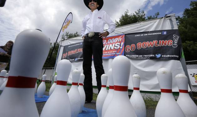 "Former NASCAR great known as ""The King,"" Richard Petty stands near bowling pins at an outdoor lane set up at Pocono Raceway, Saturday, Aug. 2, 2014, Long Pond, Pa. (AP Photo/Mel Evans)"
