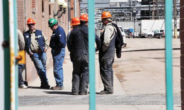 In this photo taken May 8, 2012, workers stand outside the Sinclair Oil Refinery in Sinclair, Wyo., a day after a flash fire at the facility. Three workers were injured and remained hospitalized at North Colorado Medical Center's Western States Burn Center in Greeley, Colo. Their condition improved to fair on Friday, May 11, 2012. A fourth worker was treated and released from Memorial Hospital of Carbon County in Rawlins on Tuesday. (AP Photo/The Rawlins Daily Times, Zachary Laux)
