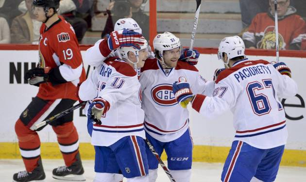 Ottawa Senators center Jason Spezza skates past Montreal Canadiens' Brendan Gallagher (11), Andrei Markov (79) and Max Pacioretty (67) as they congratulate David Desharnais on his goal during the first period of an NHL hockey game Thursday, Jan. 16, 2014, in Ottawa, Ontario. (AP Photo/The Canadian Press, Adrian Wyld)