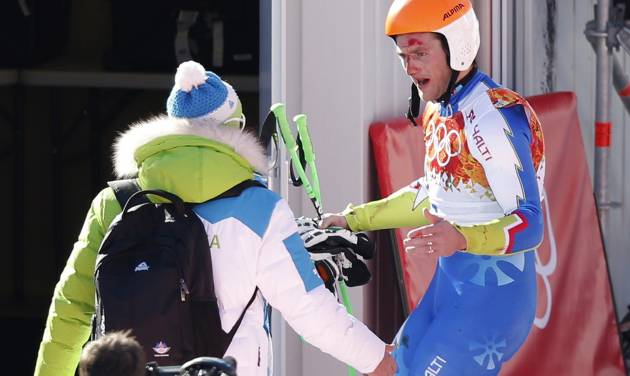 Slovenia's Rok Perko talks to a coach in the finish area after crashing in a men's downhill training run for the Sochi 2014 Winter Olympics, Saturday, Feb. 8, 2014, in Krasnaya Polyana, Russia. (AP Photo/Christophe Ena)