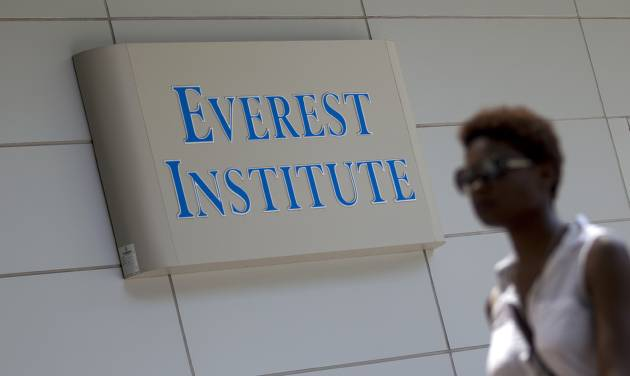 A person walks past an Everest Institute sign in a office building in Silver Spring, Md., Tuesday, July 8, 2014. The dozen campuses that for-profit education company Corinthian Colleges Inc. is closing operate under the Everest name and are scattered in 11 different states, the company announced. (AP Photo/Jose Luis Magana)