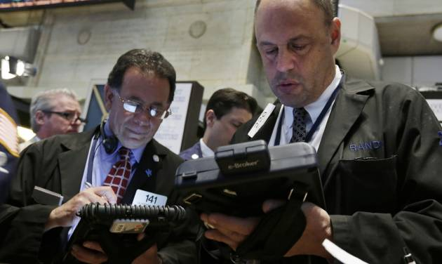 Randy Beller, right, works with fellow traders on the floor of the New York Stock Exchange Thursday, April 24, 2014. Mixed earnings from a large number of U.S. companies left the stock market without direction early Thursday, despite positive results from a handful of names including Apple and Caterpillar. (AP Photo/Richard Drew)