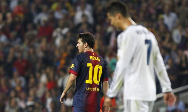 Real Madrid's Cristiano Ronaldo from Portugal, right, and FC Barcelona's Lionel Messi from Argentina, left, gesture during a Spanish La Liga soccer match at the Camp Nou stadium in Barcelona, Spain, Sunday, Oct. 7, 2012. (AP Photo/Andres Kudacki)