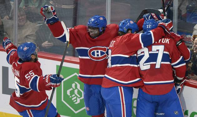 Montreal Canadiens' PK Subban (76), Francis Bouillon (55), Brandon Prust (8), and Alex Galchenyuk (27) celebrate a goal by teammate Brendan Gallagher, hidden, during the second period of  an NHL hockey game against the Buffalo Sabres in Montreal, Saturday ,Feb. 2, 2013. (AP Photo/The Canadian Press, Graham Hughes)
