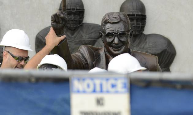 Workers handle the statue of former Penn State football coach Joe Paterno before removing the statue Sunday, July 22, 2012, in State College, Pa. The famed statue of Paterno was taken down from outside the Penn State football stadium Sunday, eliminating a key piece of the iconography surrounding the once-sainted football coach accused of burying child sex abuse allegations against a retired assistant. (AP Photo/John Beale) ORG XMIT: PAJL102