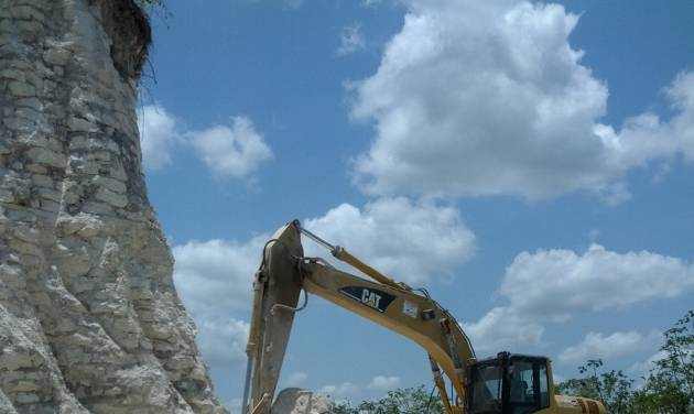 In this image released by Jaime Awe, head of the Belize Institute of Archaeology on Monday May 13, 2013, a backhoe claws away at the sloping sides of the Nohmul complex, one of Belize's largest Mayan pyramids on May 10, 2013 in northern Belize. A construction company has essentially destroyed one of Belize's largest Mayan pyramids with backhoes and bulldozers to extract crushed rock for a road-building project, authorities announced on Monday. (AP Photo/Jaime Awe)