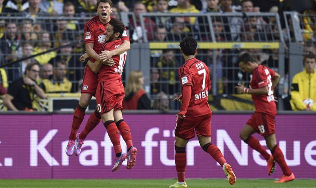 Leverkusen's Sebastian Boenisch from Poland, Hakan Calhanoglu from Turkey and Son Heung-min from South Korea, from left, celebrate the opening goal after ten seconds by Leverkusen's Karim Bellarabi, right, during the German Bundesliga soccer match between Borussia Dortmund and Bayer Leverkusen in Dortmund,  Germany, Saturday, Aug. 23, 2014.. (AP Photo/Martin Meissner)