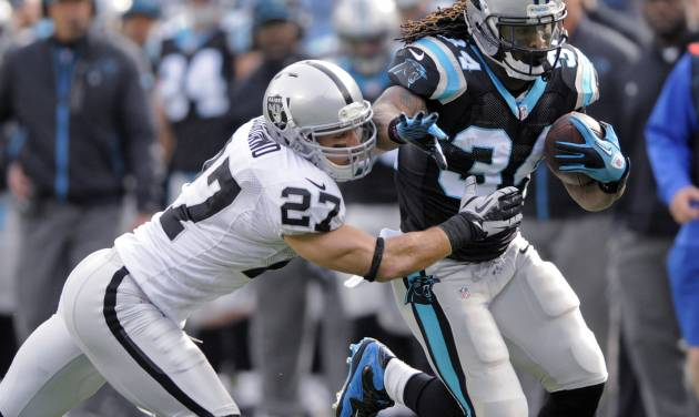 Carolina Panthers' DeAngelo Williams (34) runs as Oakland Raiders' Matt Giordano (27) tries to make the tackle during the first half of an NFL football game in Charlotte, N.C., Sunday, Dec. 23, 2012. (AP Photo/Mike McCarn)