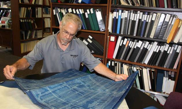 In this June 19, 2014 photo provided by Robert Gibson, shows Robert Gibson, the emergency section supervisor at the DNR's Department of Mines and Minerals, looking at maps of old coal mines at Southern Illinois University Edwardsville, in Edwardsville, Ill., that are being digitized and  by the state. Mine maps marked the locations of rooms, pillars and shafts _ necessary then and a valuable tool for state officials, homeowners and developers today because of the damage current structures can sustain if an abandoned mine begins to collapse or sag. But the DNR only has about 2,000 maps for the more than 4,000 separate mines that operated in the state, Gibson said. The state is digitizing those in its archives before they deteriorate, but also is searching for as many missing maps as possible. (AP Photo/Courtesy of Robert Gibson,Darlene Barker
