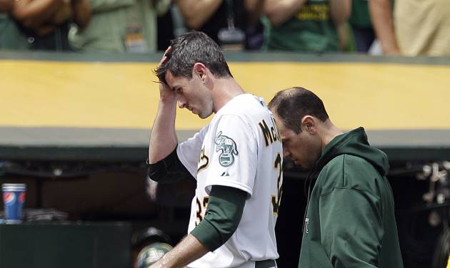 FILE - In this Sept. 5, 2012, file phoro, Oakland Athletics pitcher Brandon McCarthy leaves the field with a trainer after being hit in the head by a ball hit by Los Angeles Angels' Erick Aybar during a baseball game in Oakland, Calif. Big league pitchers could experiment with protective hat liners next season, hoping they can absorb the shock of batted balls such as the ones that struck McCarthy and Doug Fister in the head. Major League Baseball medical director Dr. Gary Green presented ideas to executives, physicians and trainers at the winter meetings this week. (AP Photo/Ben Margot, File)