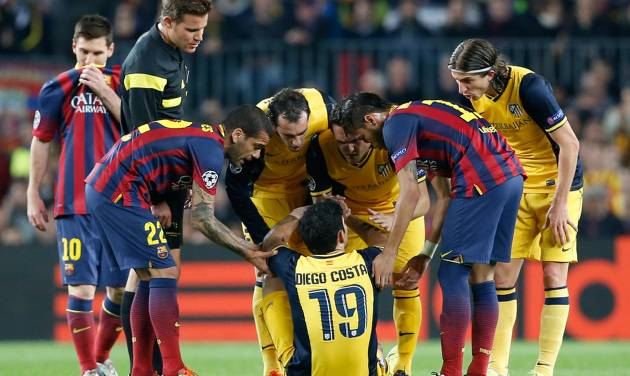 Players check on Atletico's Diego Costa, center, after he injured himself during a first leg quarterfinal Champions League soccer match between Barcelona and Atletico Madrid at the Camp Nou stadium in Barcelona, Spain, Tuesday April 1, 2014. (AP Photo/Emilio Morenatti)