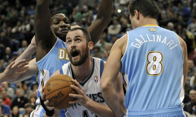 Minnesota Timberwolves' Kevin Love, center, eyes the basket between Denver Nuggets' Danilo Gallinari, right, of Italy, and another defender in the first half of an NBA basketball game on Wednesday, Nov. 21, 2012, in St. Paul. it was Love's return to the lineup for the first time in regular season play after suffering a broken hand. (AP Photo/Jim Mone)