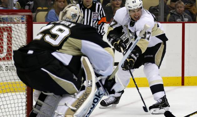 Pittsburgh Penguins White Team's Sidney Crosby (87) backhands a pass in front of Black Team goalie Marc-Andre Fleury (29) during the second period of an NHL hockey scrimmage in Pittsburgh, Wednesday, Jan. 16, 2013. (AP Photo/Gene J. Puskar)
