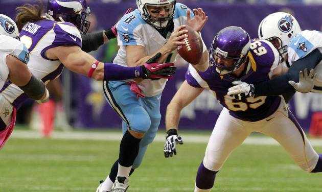 Tennessee Titans quarterback Matt Hasselbeck, center, scrambles between Minnesota Vikings defensive end Brian Robison, second from left, and defensive end Jared Allen (69) during the first half of an NFL football game on Sunday, Oct. 7, 2012, in Minneapolis. (AP Photo/Genevieve Ross)