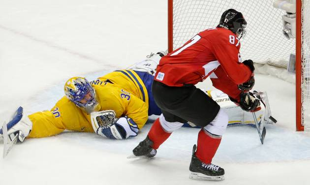 Sidney Crosby of Canada (87) scores on Goalkeeper Henrik Lundqvist of Sweden (30) during the second period in the gold medal men's ice hockey game at the 2014 Winter Olympics, Sunday, Feb. 23, 2014, in Sochi, Russia. (AP Photo/Mark Humphrey)