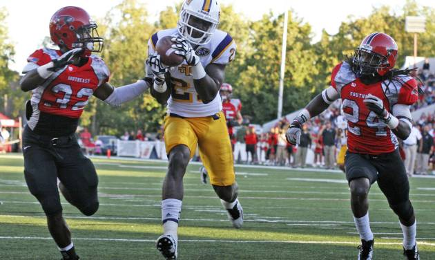 In this photo taken Sept. 22, 2012 and provided by Tennessee Tech University, Tech wide receiver Da'Rick Rogers (21) scores a touchdown between Southeast Missouri State defenders Josh Coleman (32) and Kweku Arkorful (24) during a college football game in Cape Girardeau, Mo. One year ago, Rogers was an all-Southeastern Conference receiver performing in one of college football's largest stadiums. Now the former Tennessee star plays in front of fewer than 10,000 fans at Tennessee Tech. (AP Photo/Tennessee Tech University)