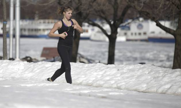 A runner runs along the lake shore Wednesday, Feb. 19, 2014, in Chicago. Weeks of subfreezing weather are giving way, at least briefly, to temperatures in the 50s, putting cities on guard for flooding, roof collapses and clogged storm drains. (AP Photo/Kiichiro Sato)