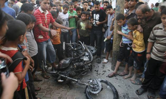 """Palestinians gather a round the wreckage of motorcycle following an Israeli air strike in Rafah, southern Gaza Strip, Sunday, Oct. 7, 2012. Israel's military says it has fired on two Gaza members of an al-Qaida-inspired group identified as having been involved in rocket attacks and an infiltration from Egypt. Palestinians say one man was killed. The military said they were involved in """"extensive terrorist activity,"""" including an attack in June where two gunmen crossed into Israel from the Sinai desert and killed a civilian. Israel did not say whether it hit the two. Ashraf al-Kidra, a Palestinian health official in Gaza said one man was killed and another injured Sunday when their motorcycle was hit by aircraft in the south of the Hamas-controlled territory. Israel and Hamas have mostly kept an unwritten truce since a short war over three years ago. Attacks have persisted but at a much lower rate. (AP Photo/Eyad Baba)"""