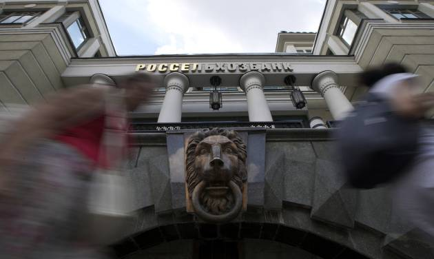 People walk past the headquarters of Russian Agricultural Bank in downtown Moscow, Russia, on Wednesday, July 30, 2014. The European Union approved dramatically tougher economic sanctions Tuesday, July 29, against Russia, followed swiftly by a new round of U.S. penalties. Among the targets were three Russian banks: the Bank of Moscow, Russian Agricultural Bank and VTB Bank, Russia's second largest bank. (AP Photo/Ivan Sekretarev)